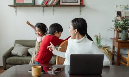 A lady handling two kids disturbing while working at home